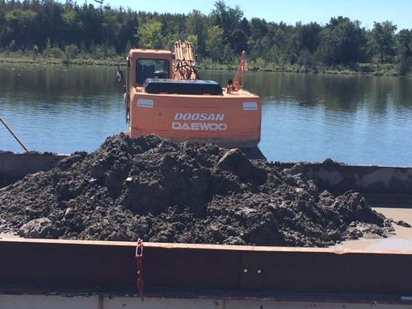 topsoil on top of barge after being dredged from the bottom of a Kettle Lake